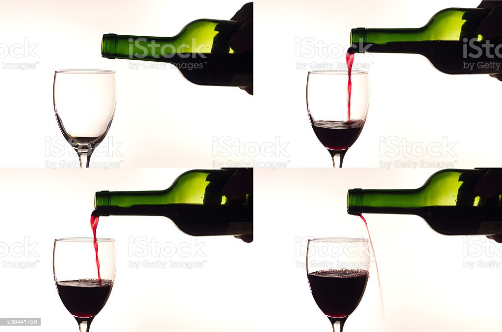 Pouring red wine into a glass stock photo