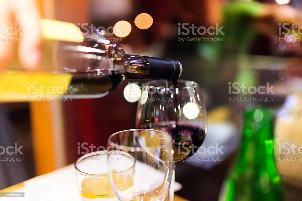 Pouring red wine into the glass stock photo