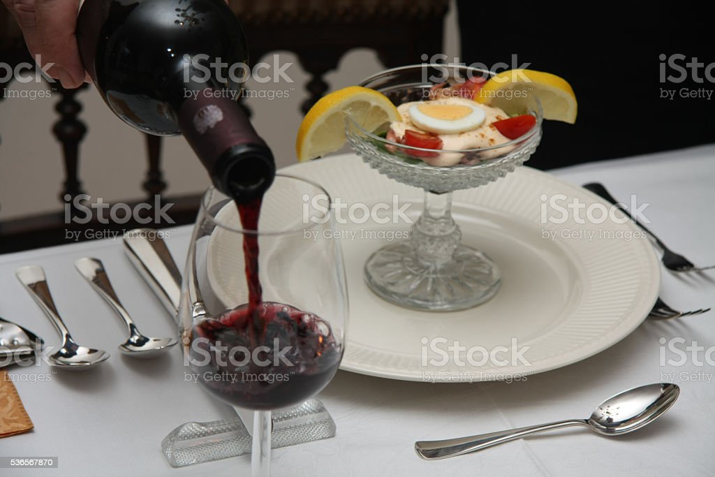 pouring red wine on a dining table stock photo
