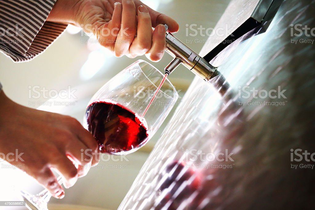 Pouring red wine out of inox wine tank. stock photo