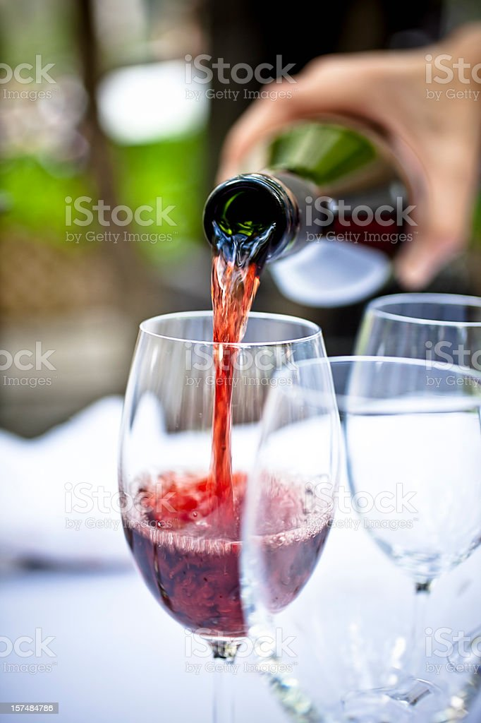 Pouring red wine with three glasses present royalty-free stock photo