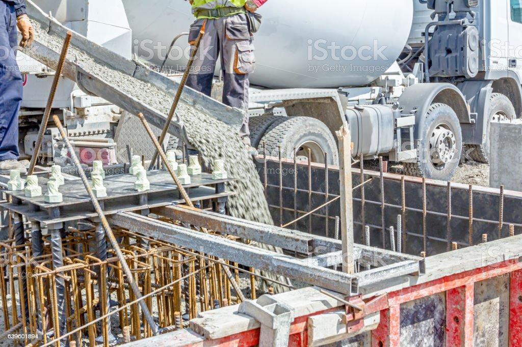 Pouring reinforced concrete in foundation mold stock photo