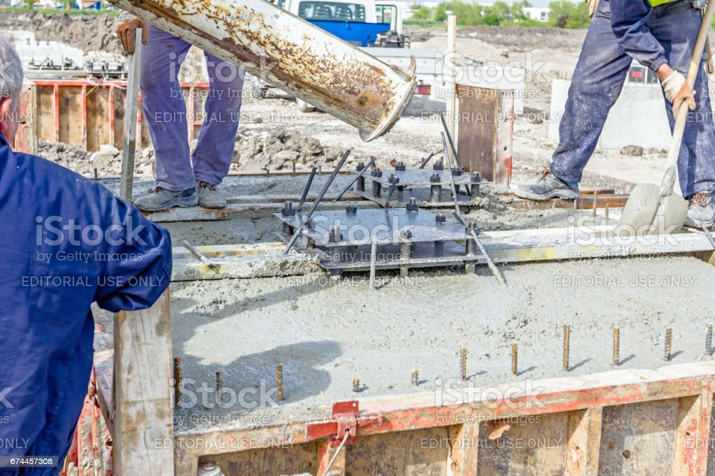 Pouring reinforced concrete in foundation mold. stock photo