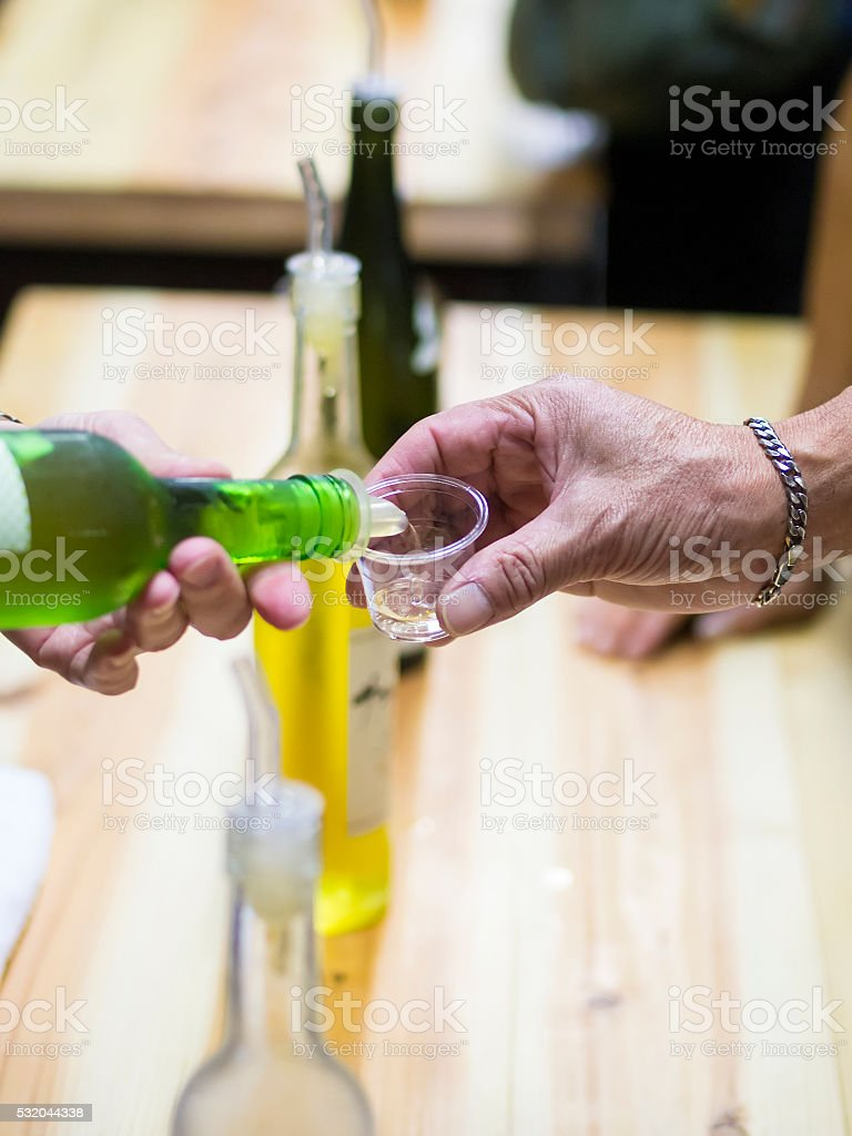 Pouring Sake from bottle to small plastick glas stock photo