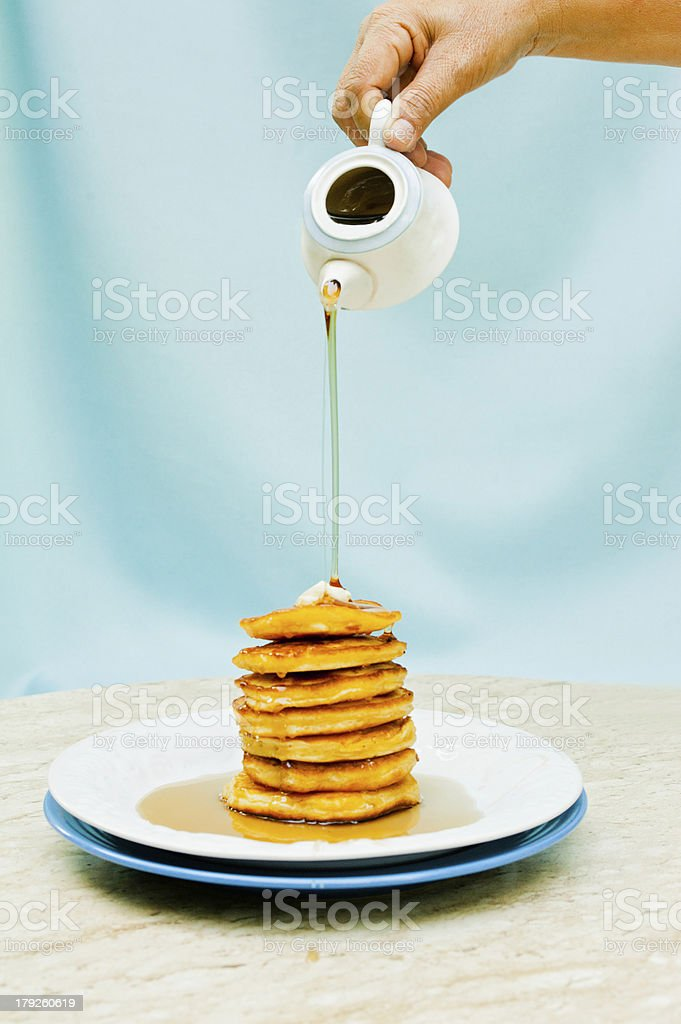 Pouring Syrup Over a Stack of Pancakes stock photo