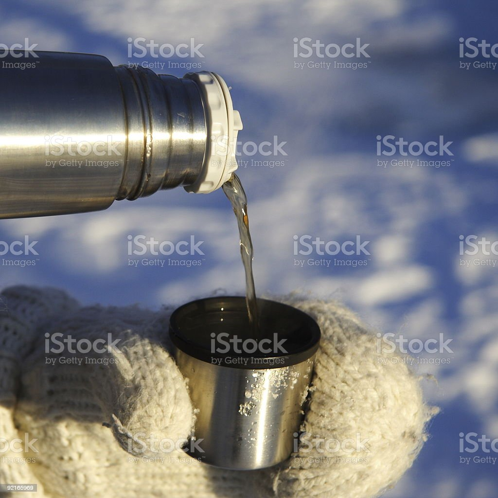 pouring tea drink outdoors in winter stock photo