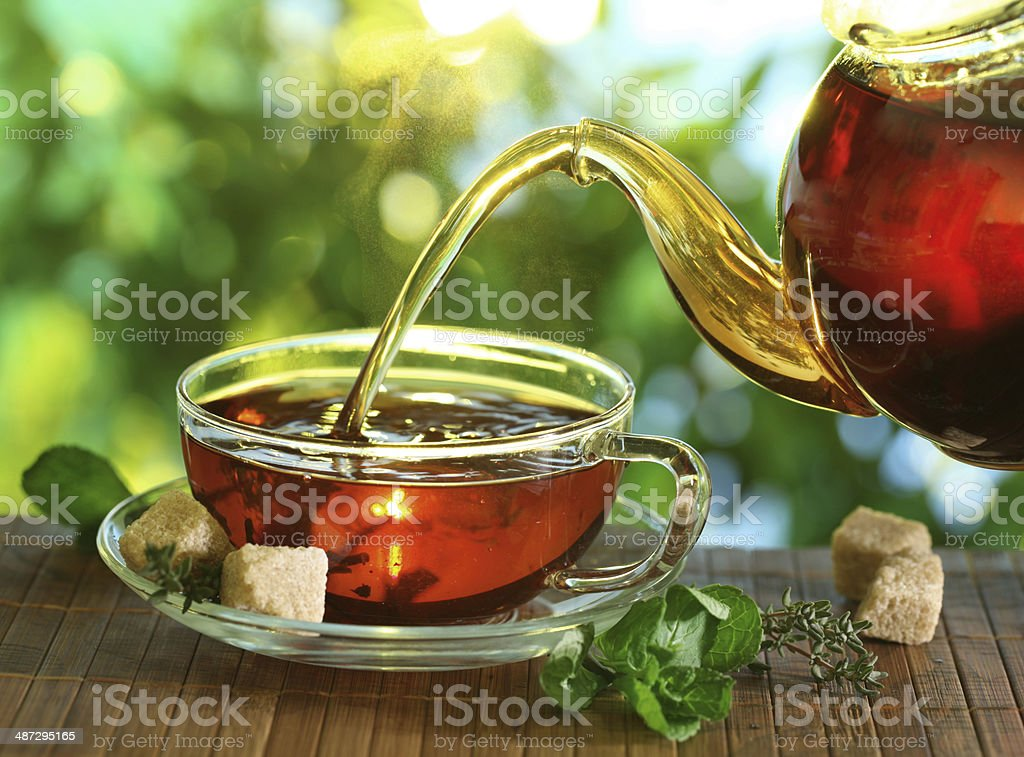 Pouring tea from a teapot into a cup. stock photo