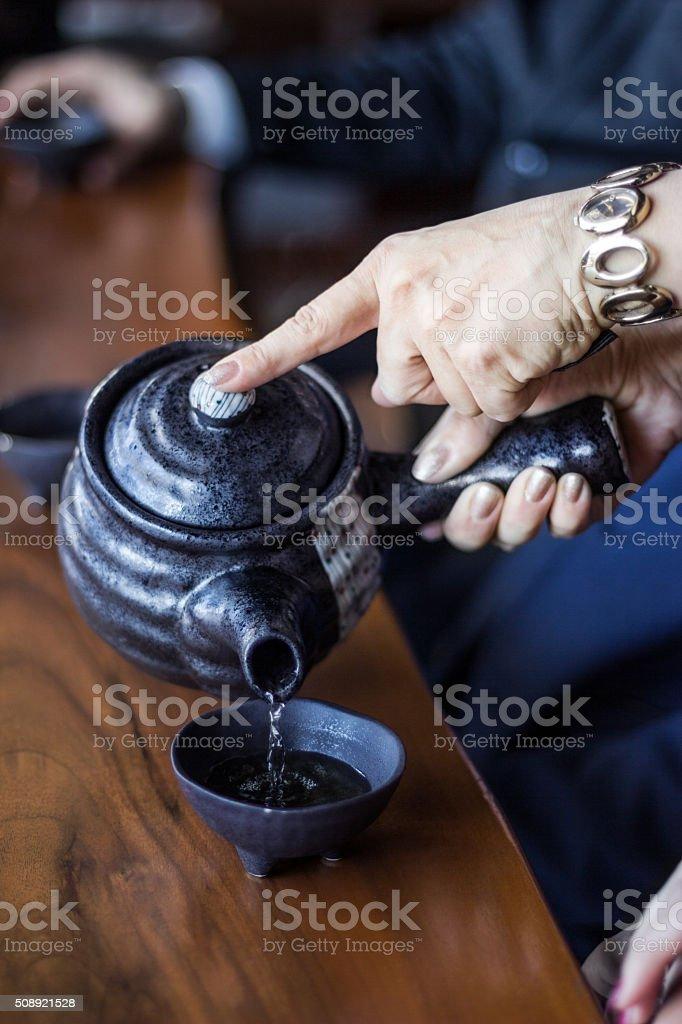 Pouring tea from teapot stock photo