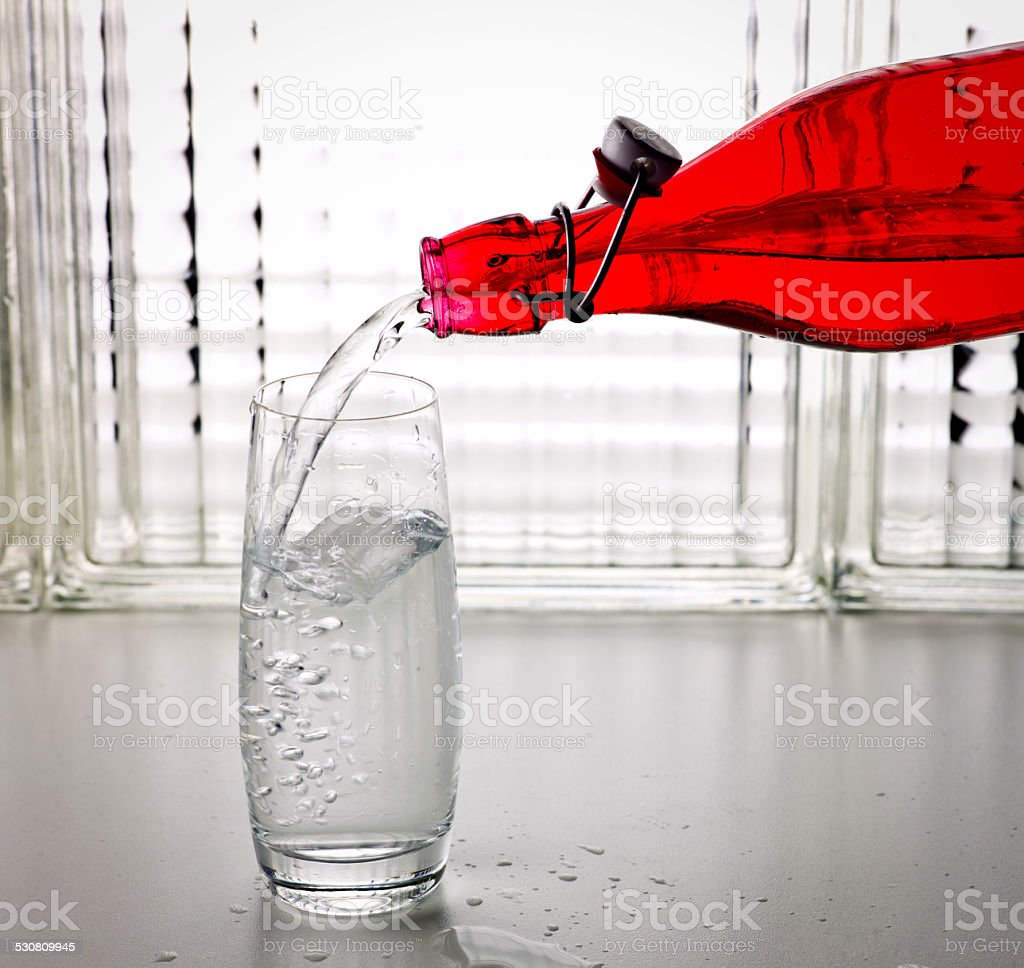 Pouring Water from a Bottle to a Glass. stock photo