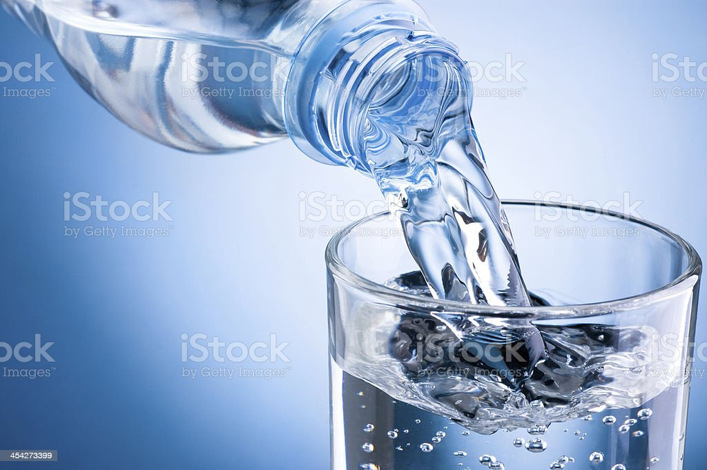 Pouring water from bottle into glass on blue background stock photo