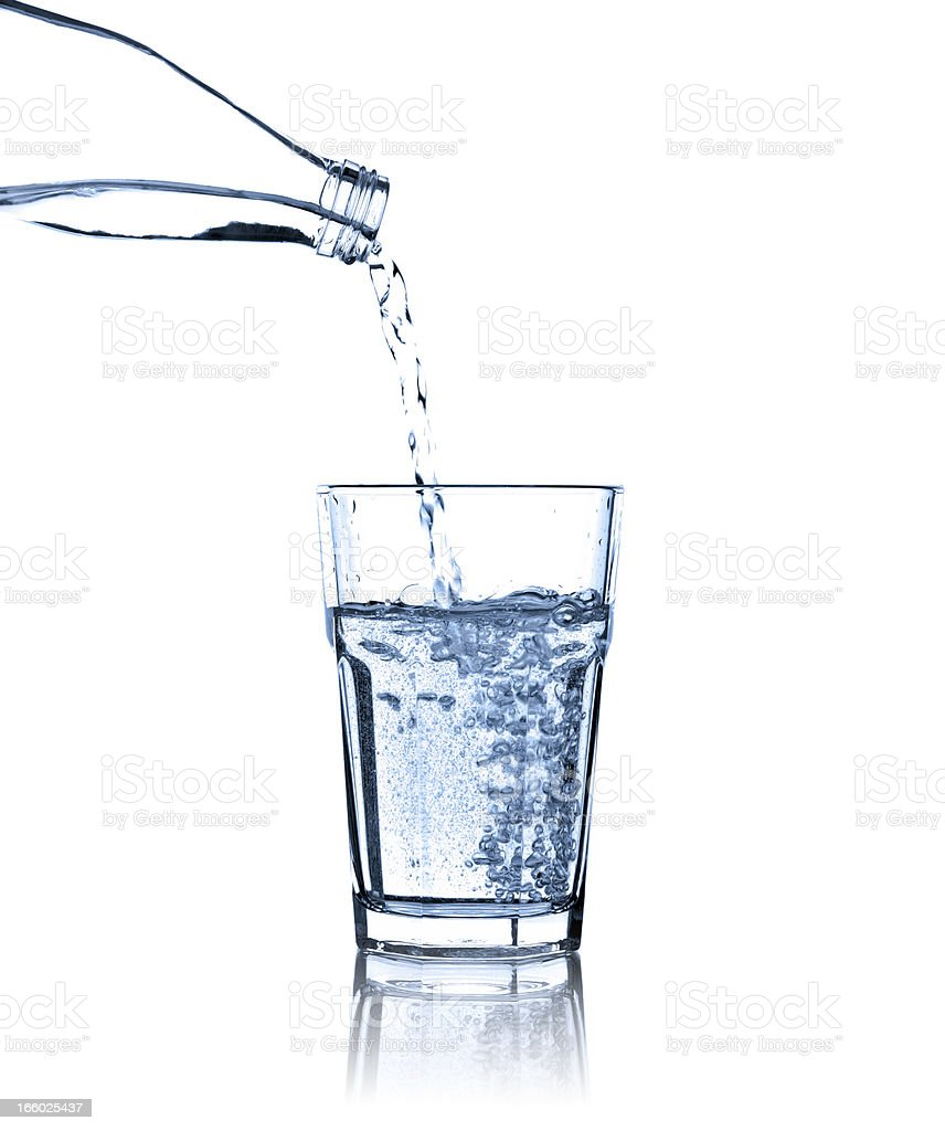Pouring water from bottle into glass, studio shot, isolated stock photo