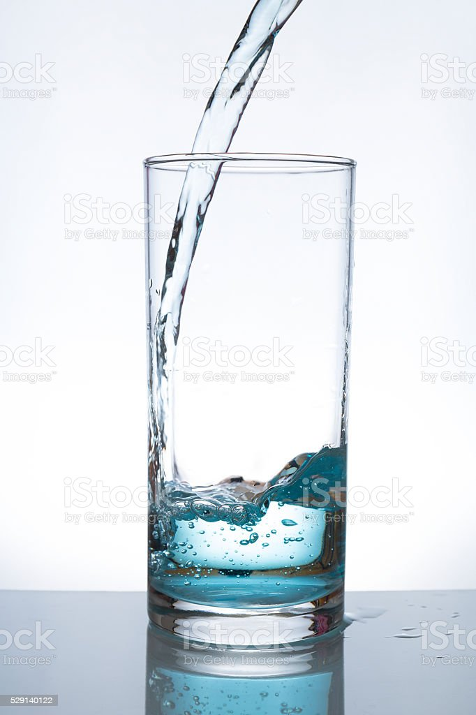 Pouring water from into glass stock photo