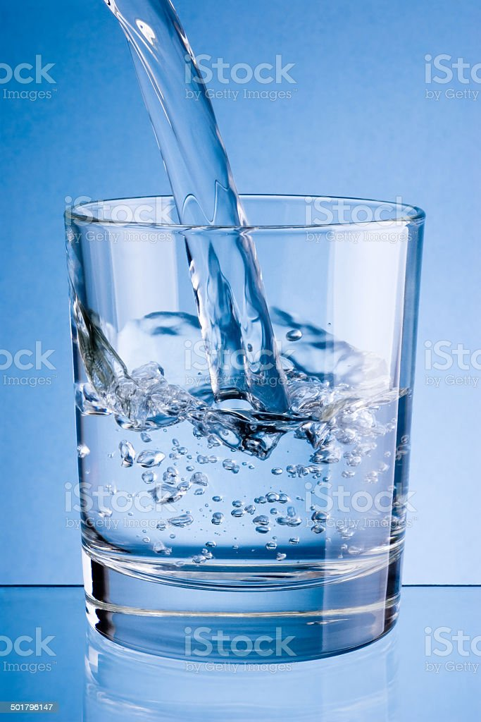 Pouring water into glass on a blue background stock photo
