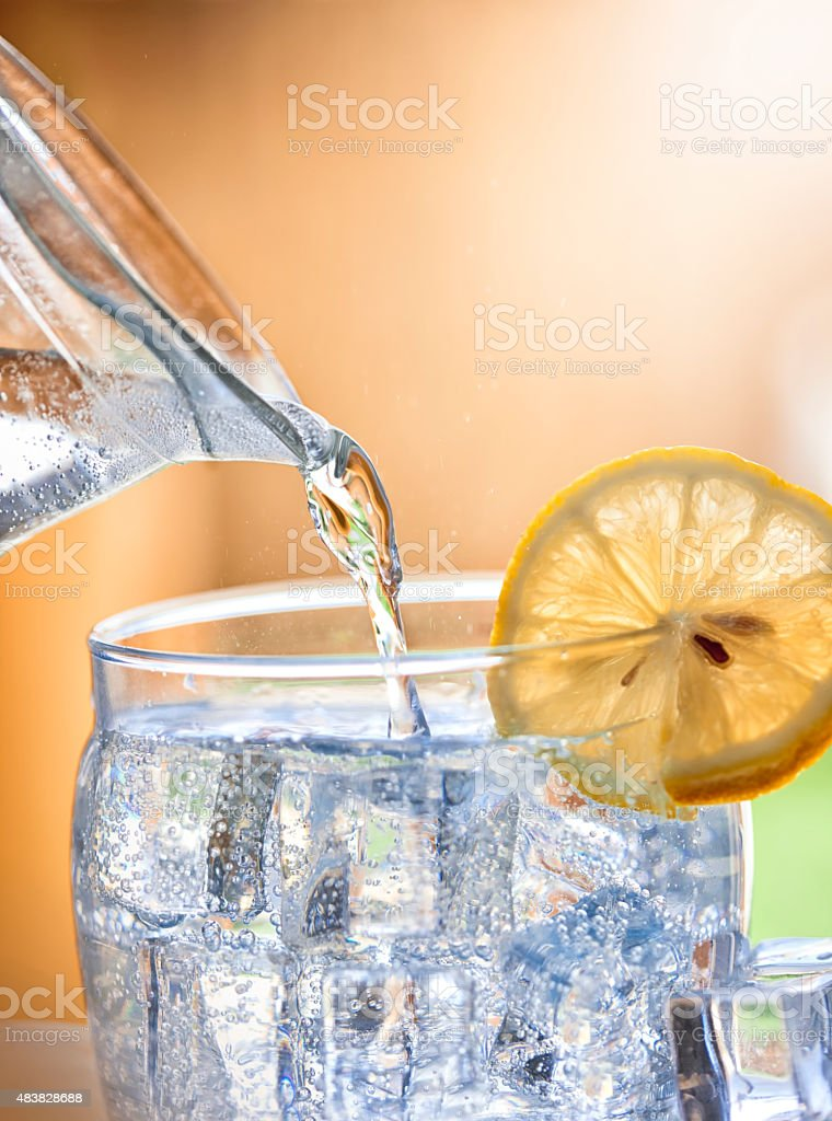 Pouring water  into glass stock photo
