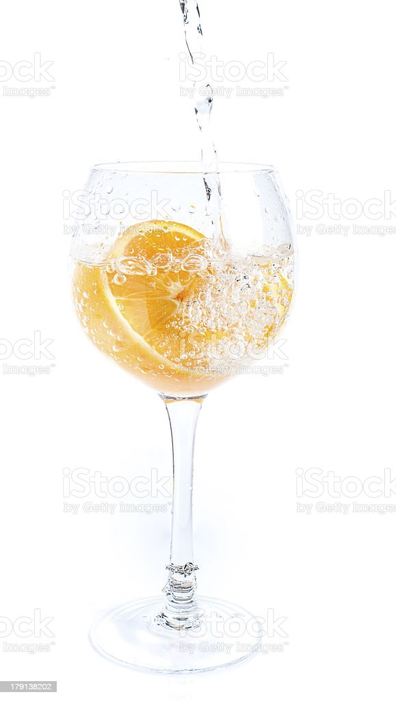 Pouring Water into Orange In Glass royalty-free stock photo