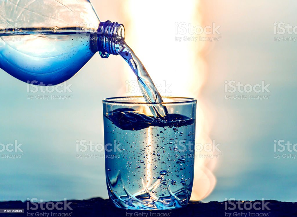 pouring water into the glass from a plastic bottle stock photo