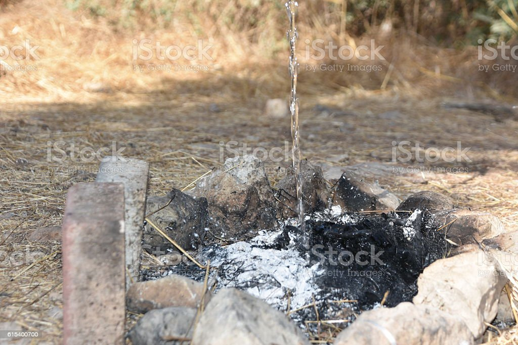 Pouring water on the campfire stock photo