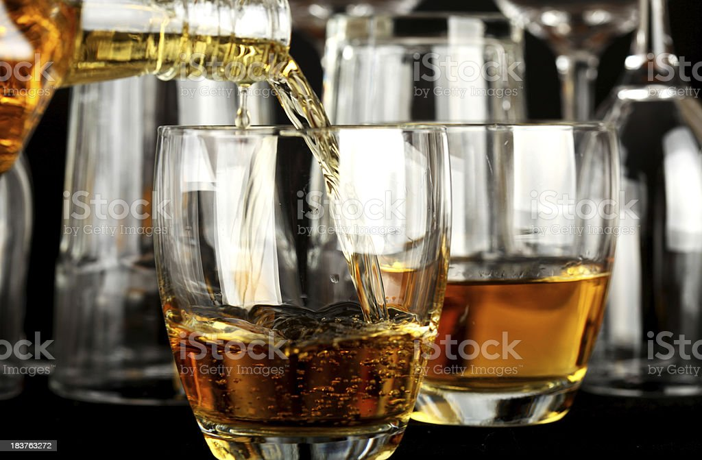 Pouring whiskey in a glass stock photo