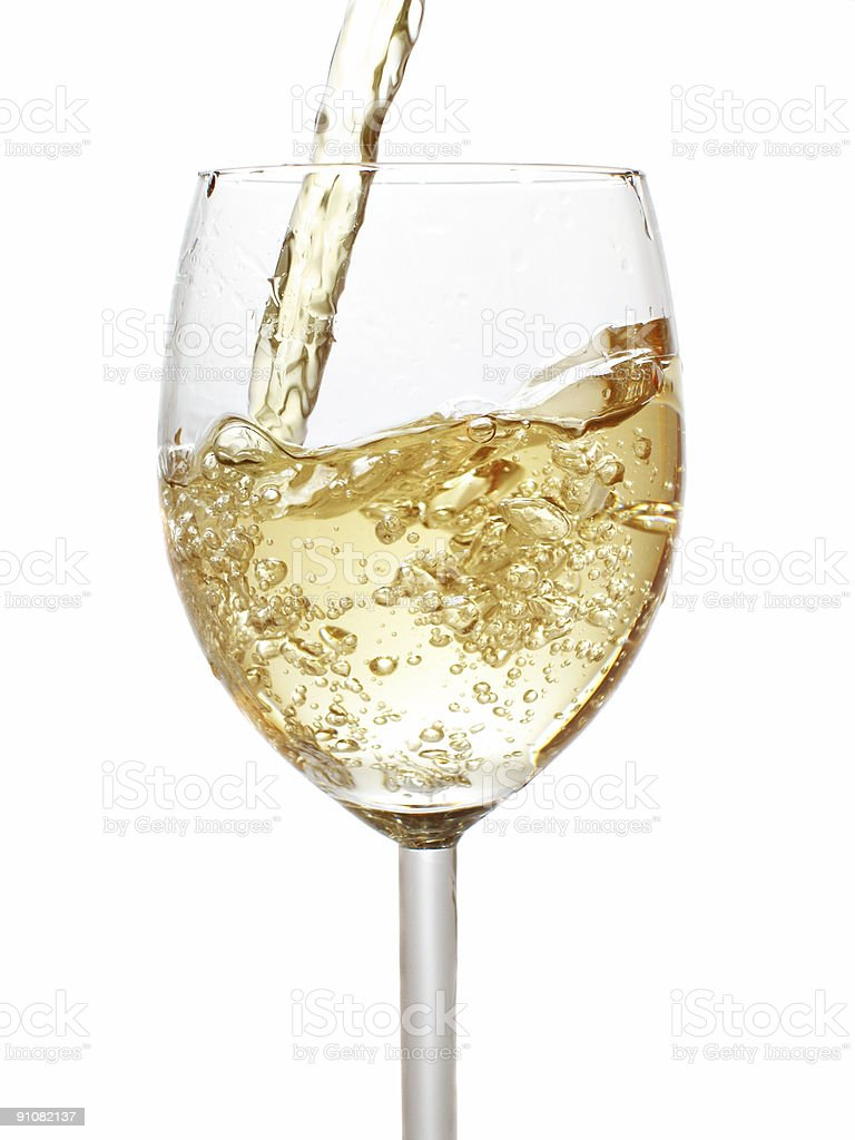 Pouring white wine into a crystal wine glass stock photo