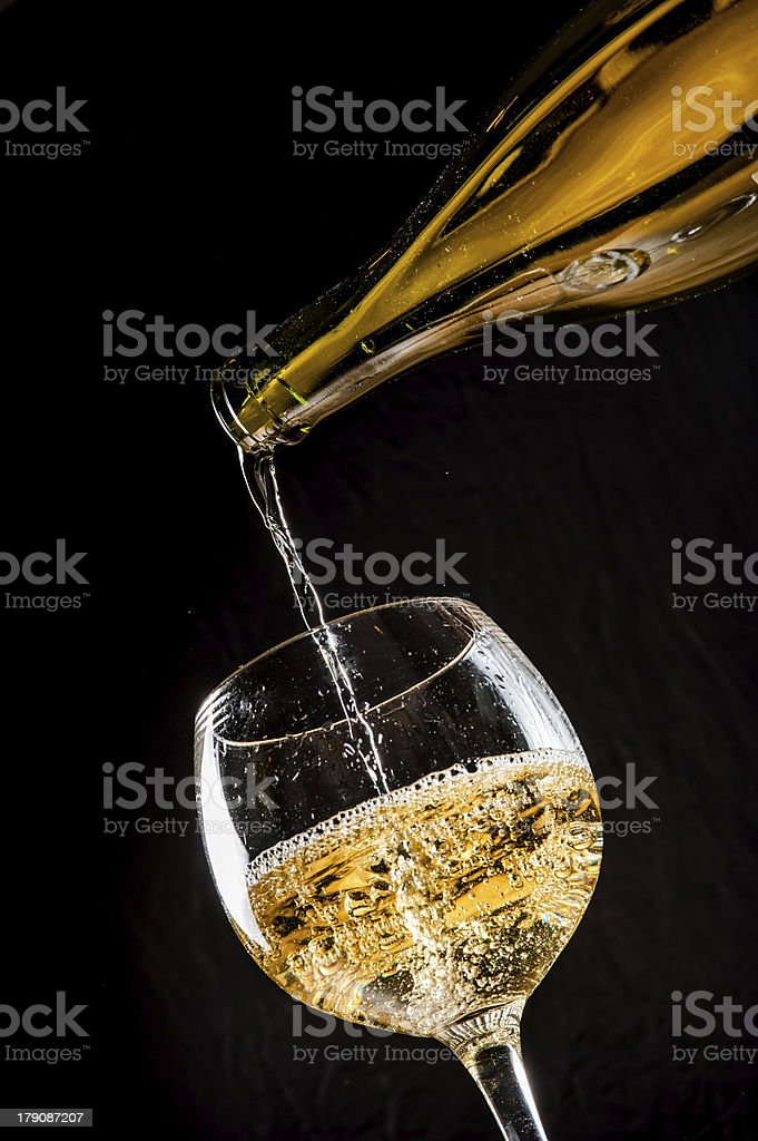 Pouring white wine into glass royalty-free stock photo