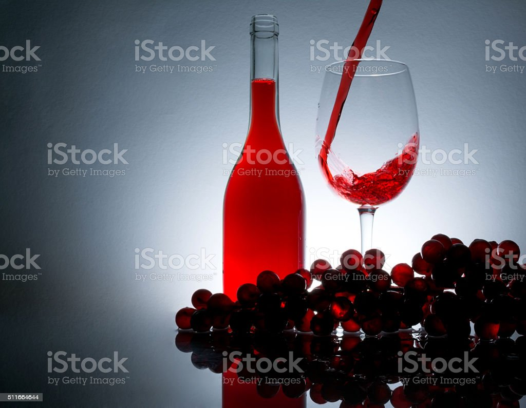 pouring wine in a glass, bottle of wine and grapes, reflection stock photo