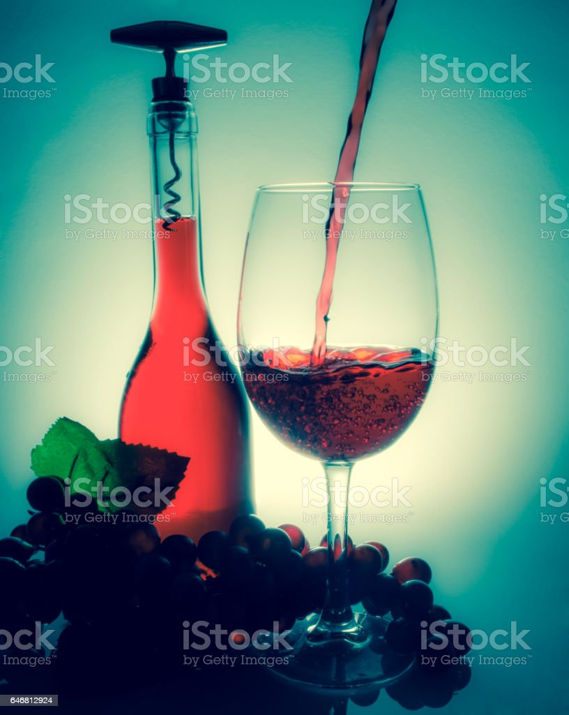 Pouring wine in a glass next to a bottle of wine and grapes on a table. Old retro vintage style. stock photo