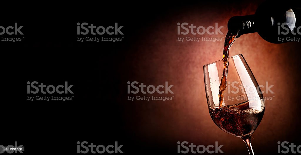 Pouring wine on brown stock photo