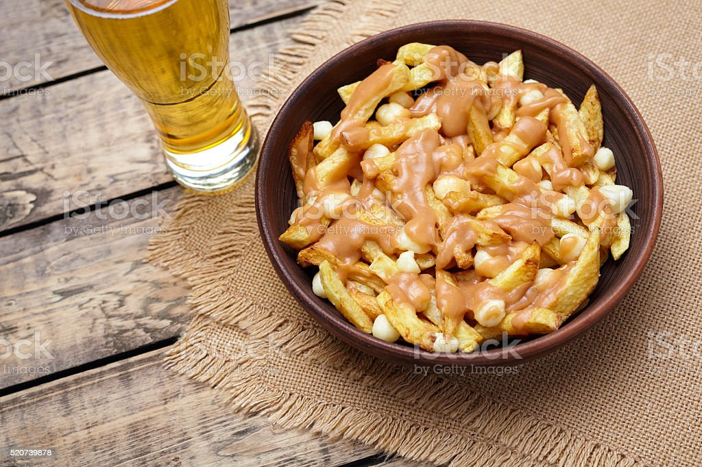 Poutine Canadian meal with fries, curd cheese, beer and gravy stock photo