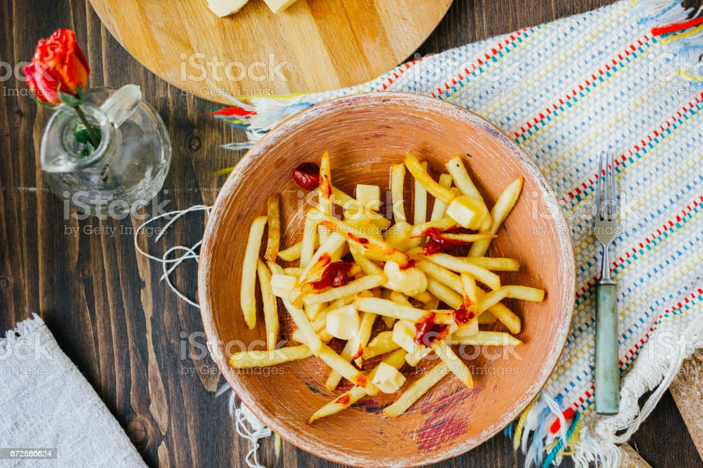 Poutine fries on black surface. Canadian dish with potatoes, cheese and sauce. stock photo