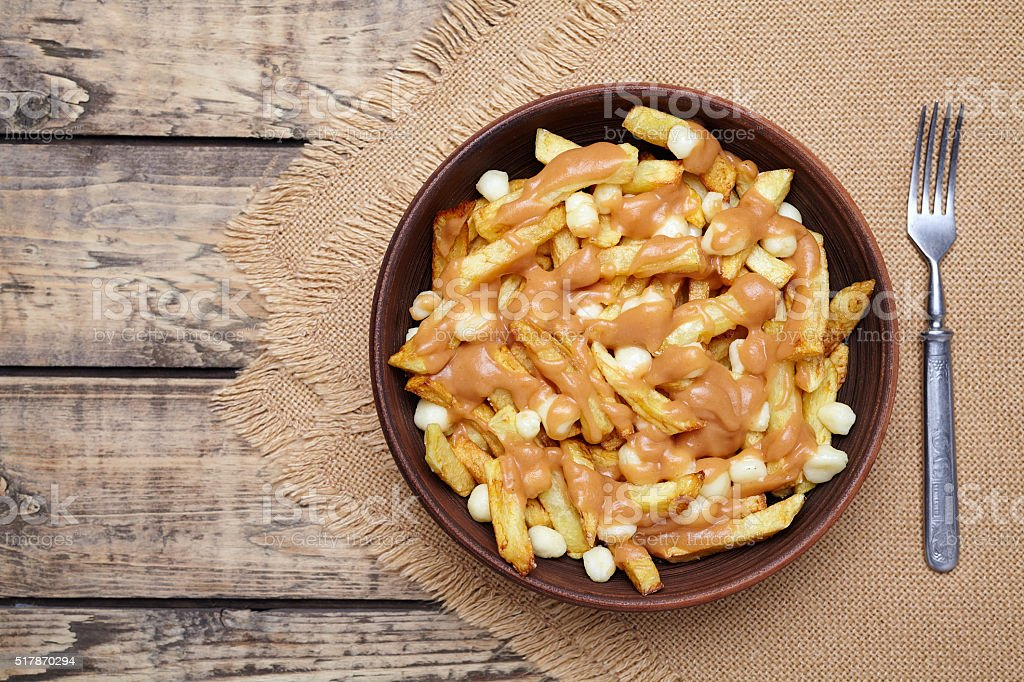 Poutine traditional Canadian meal with fries, curd cheese and sauce stock photo