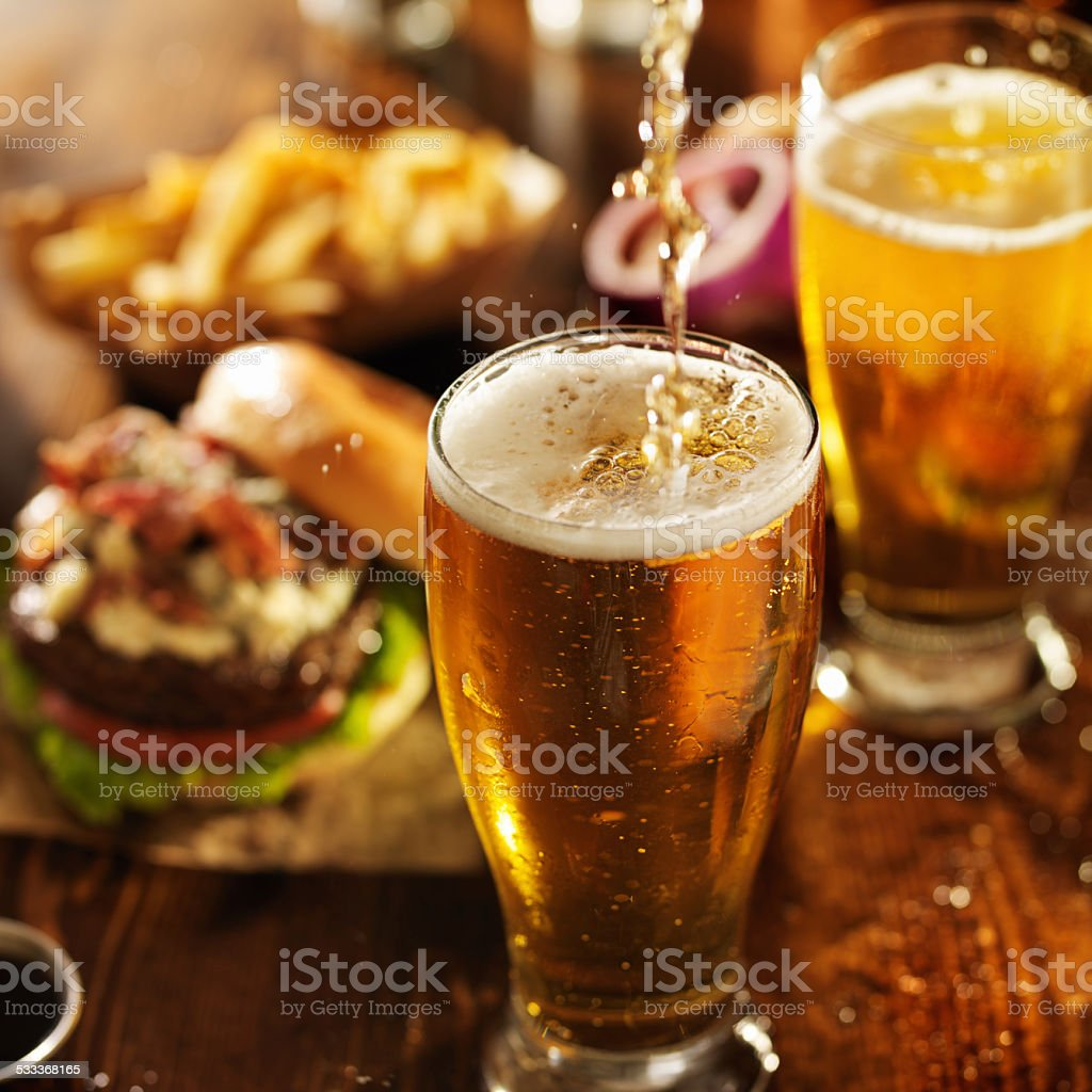 pouting beer into glass with burgers stock photo