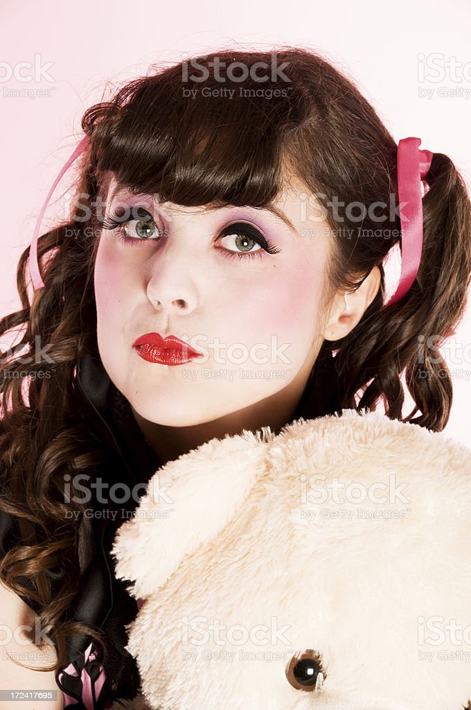 Pouting porcelain doll model with beige bear. royalty-free stock photo
