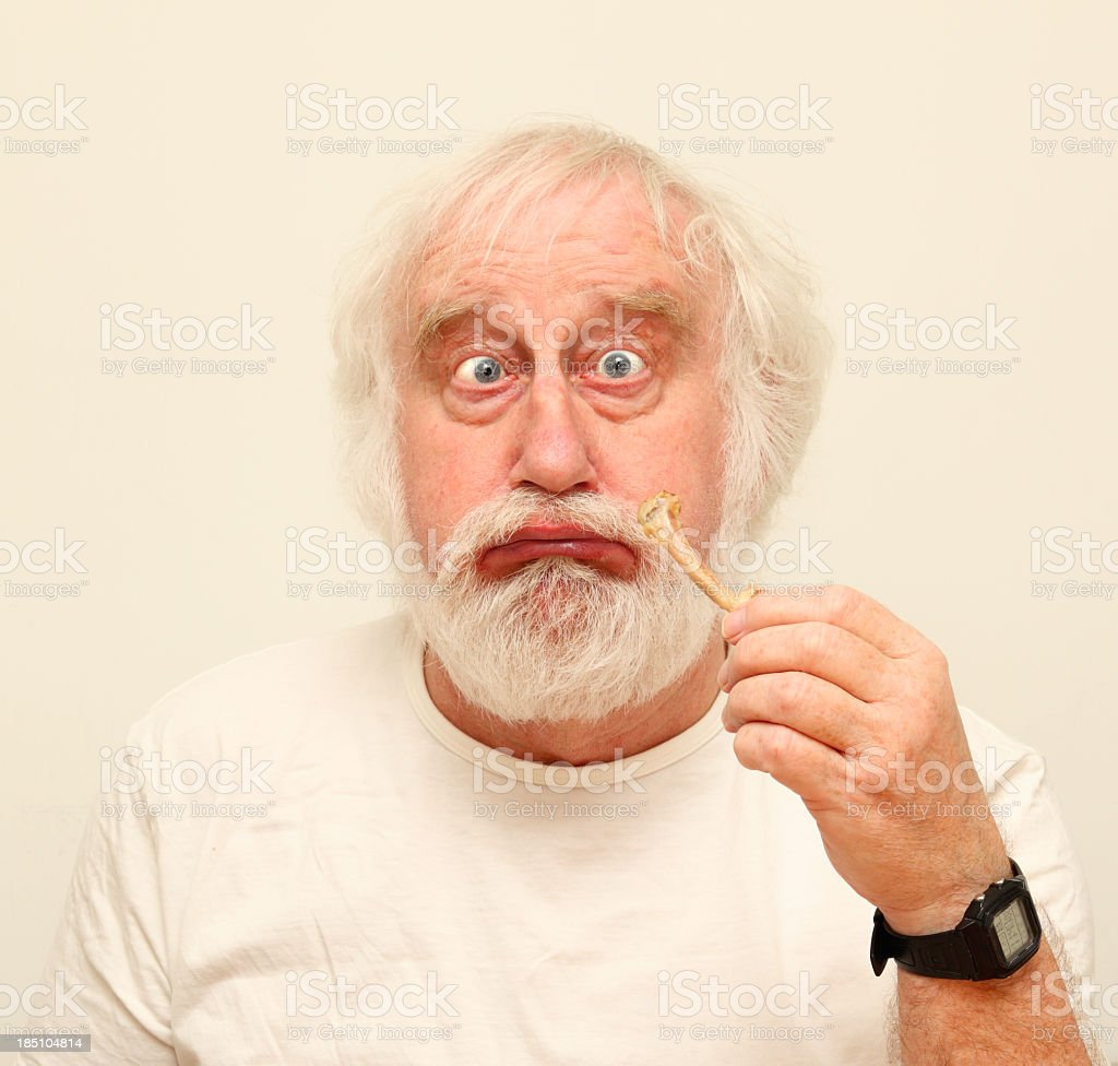 pouting senior white haired male cross-eyed eating chicken bone stock photo