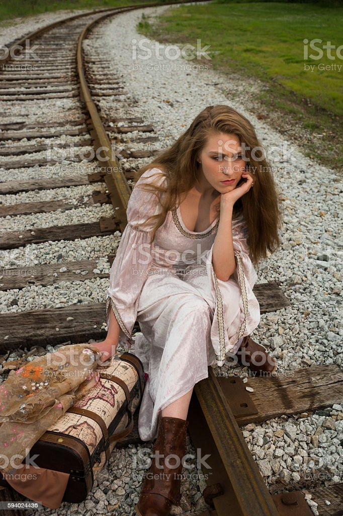 Pouting young woman waiting on train tracks stock photo