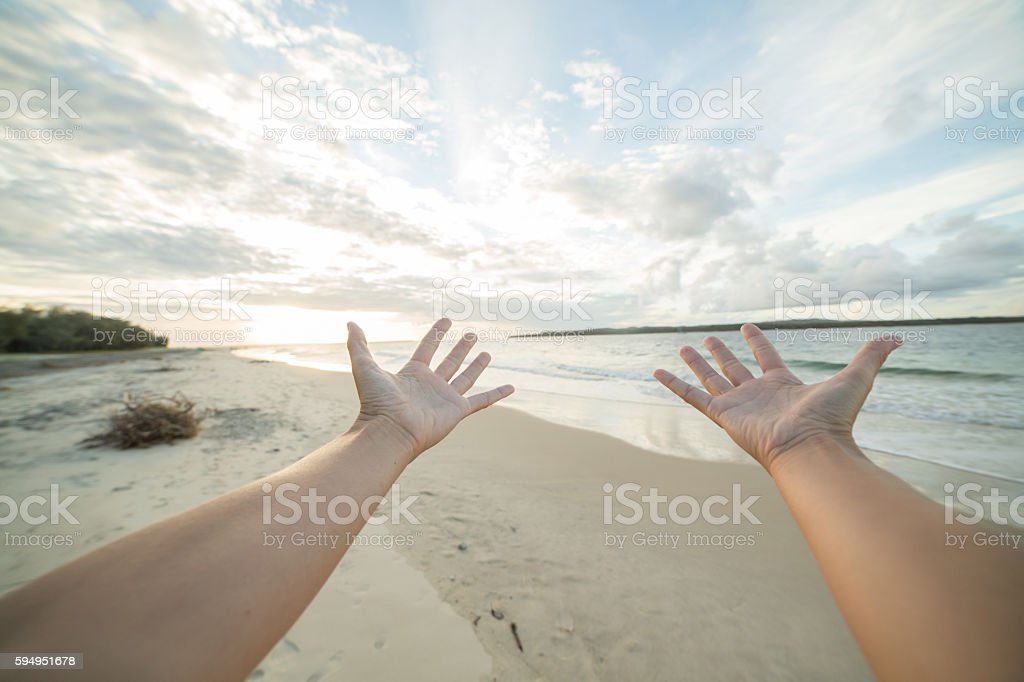 Pov of female arms outsretched on beach stock photo
