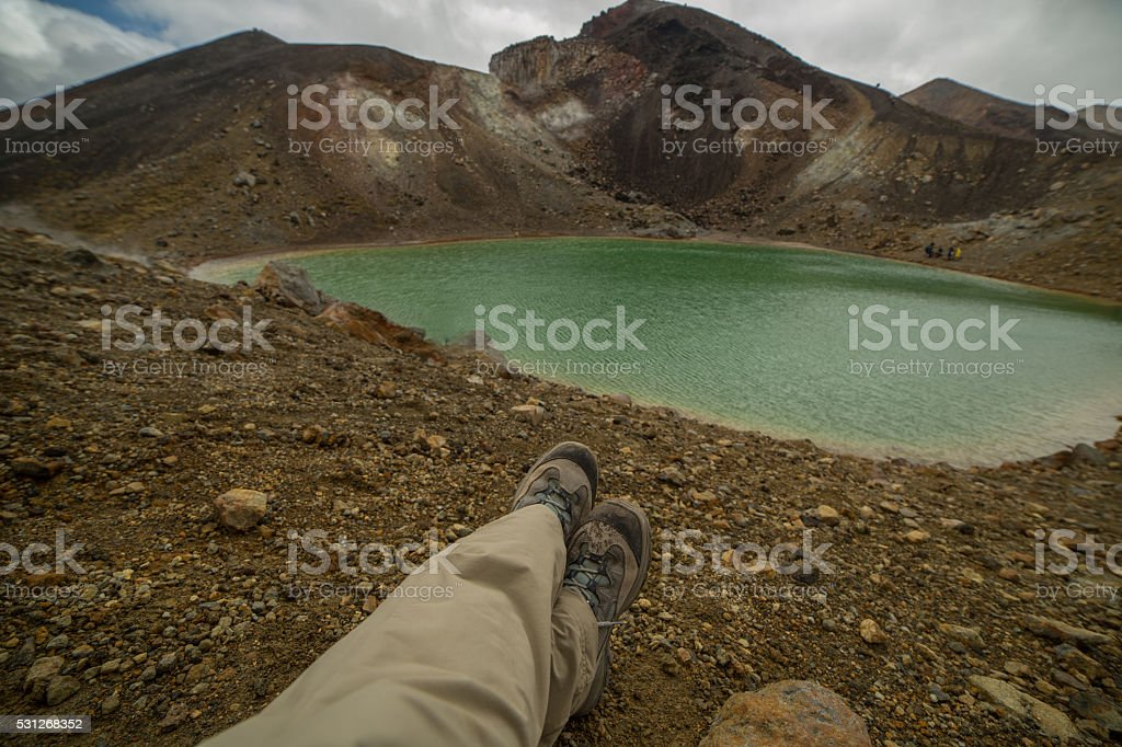Pov of hiker relaxing by the mountain lake stock photo