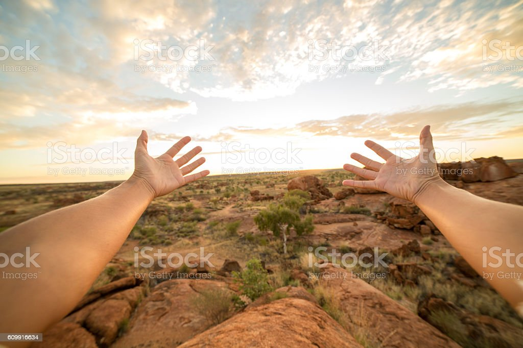 Pov of person stretching arms towards Devil's Marbles at sunrise stock photo