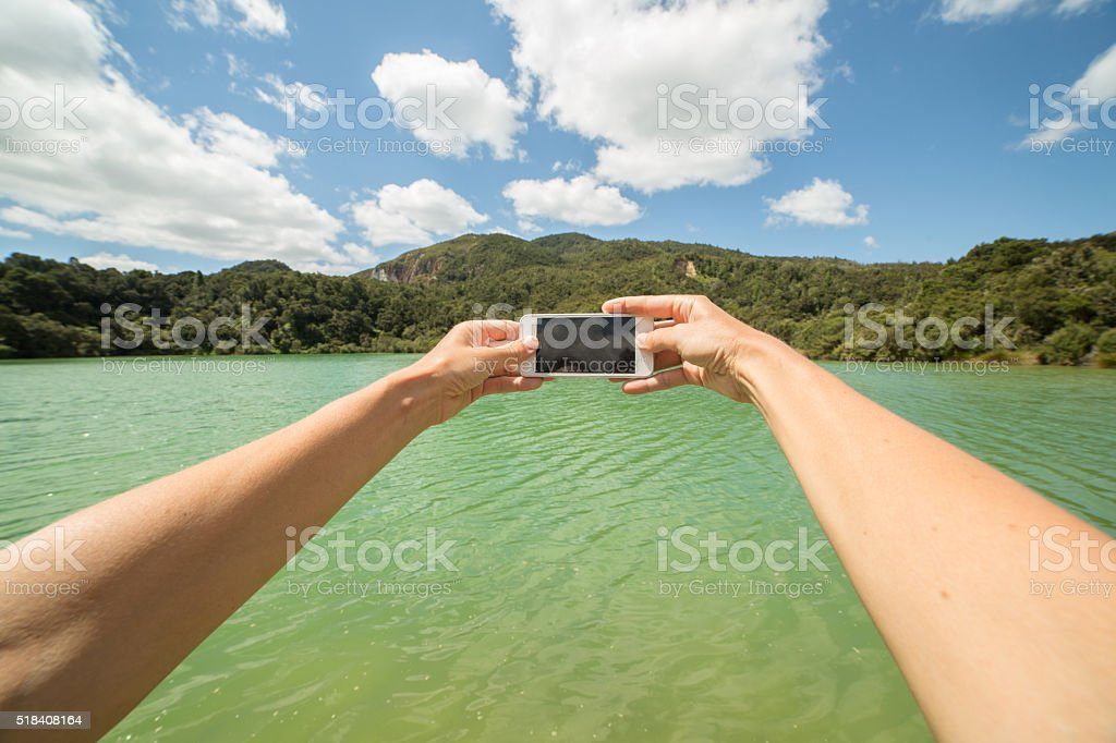 Pov of person taking picture of lake using mobile phone-NZ stock photo