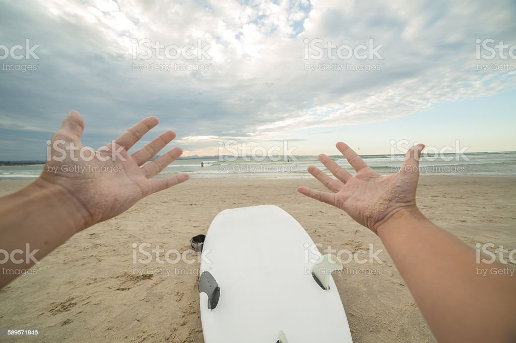 Pov of surfer sitting on beach with surfboard stock photo