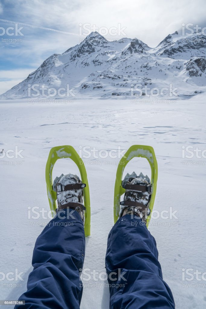Pov of young man snowshoeing in Switzerland stock photo