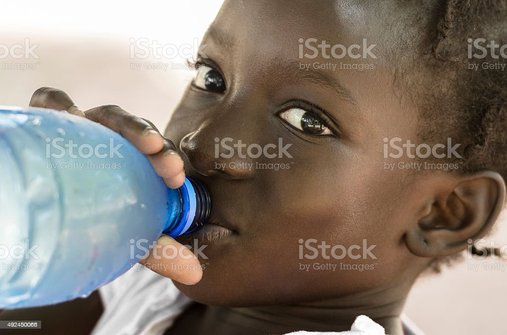 Poverty Symbol: African Black Girl Drinking Heathy Fresh Water stock photo