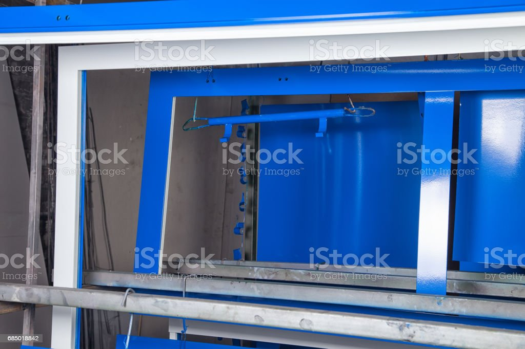 Powder coating and drying of metal blue doors stock photo