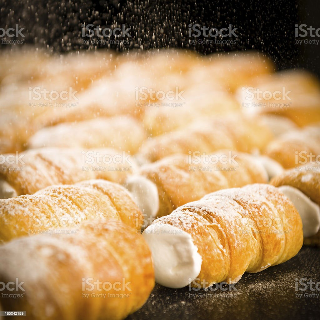 Powder sugar falling on to cream horns stock photo