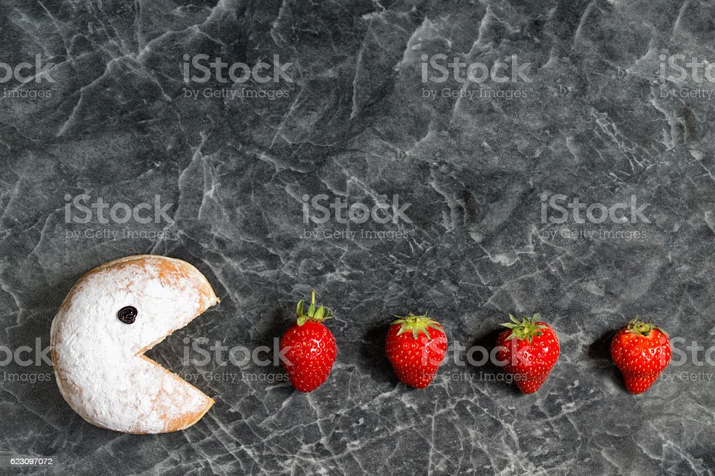 Powdered donut with smiley face eating strawberries stock photo