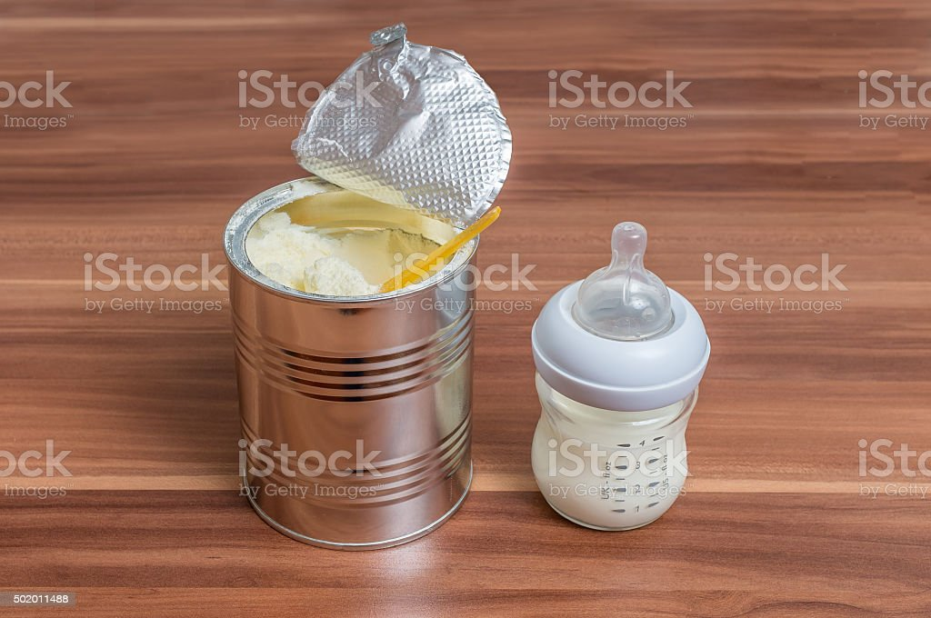 Powdered milk formula in can and bottle for feeding baby stock photo