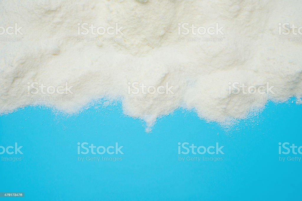 powdered milk on blue background with copy space stock photo