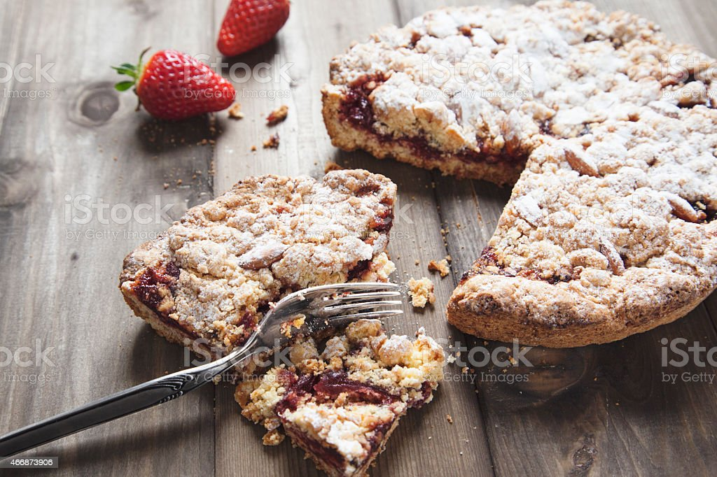 Powdered sugar strawberry tart on wooden kitchen table stock photo