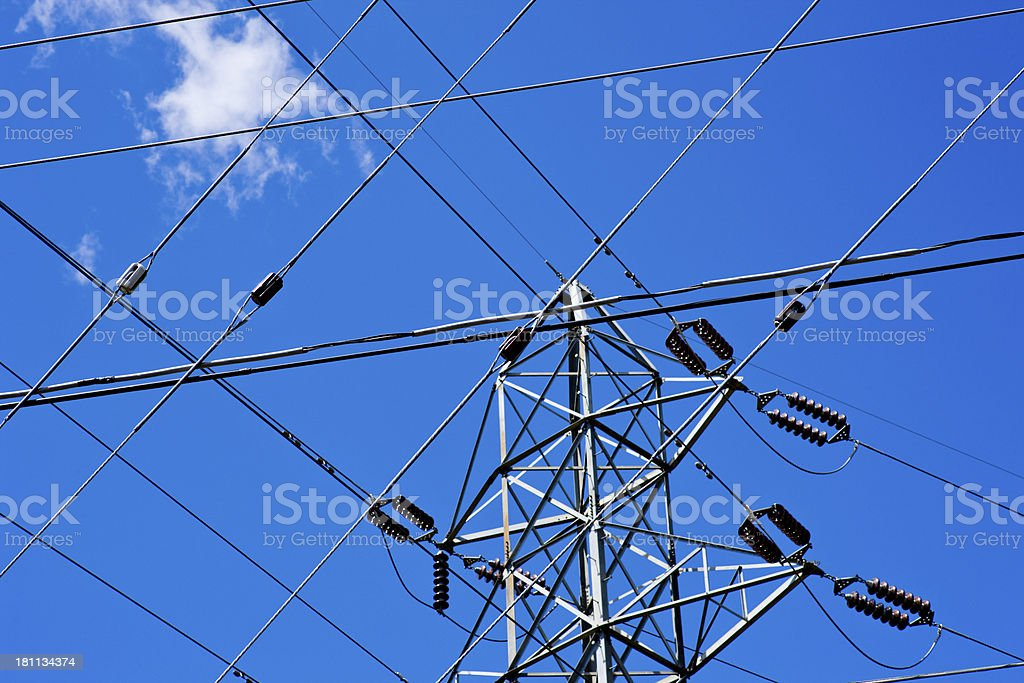 Power and phone lines cross in a blue sky royalty-free stock photo