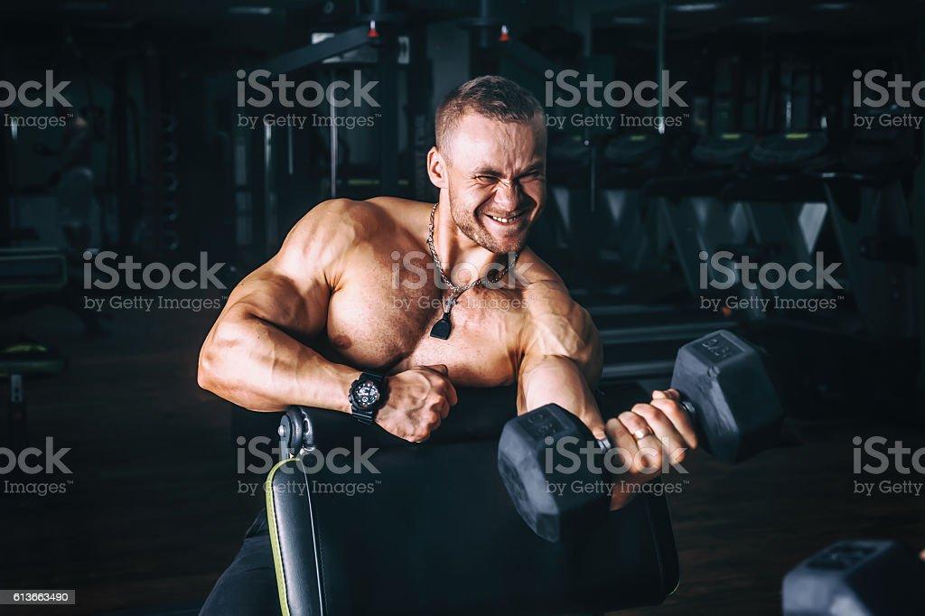 power athletic guy bodybuilder, execute exercise with dumbbells, in dark stock photo