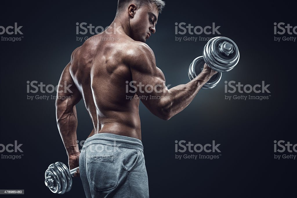 Power athletic man in training pumping up muscles with dumbbells stock photo
